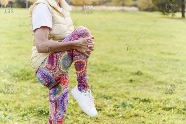 Mature woman doing warm up exercise in public park