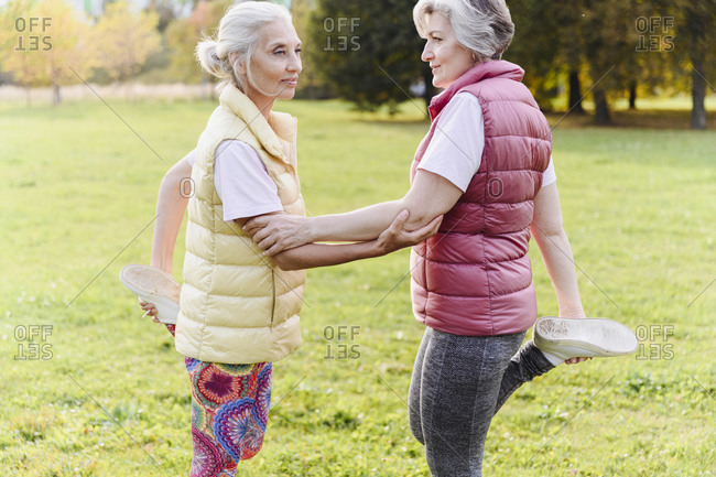 Mature female friends doing warm up exercise together at public park