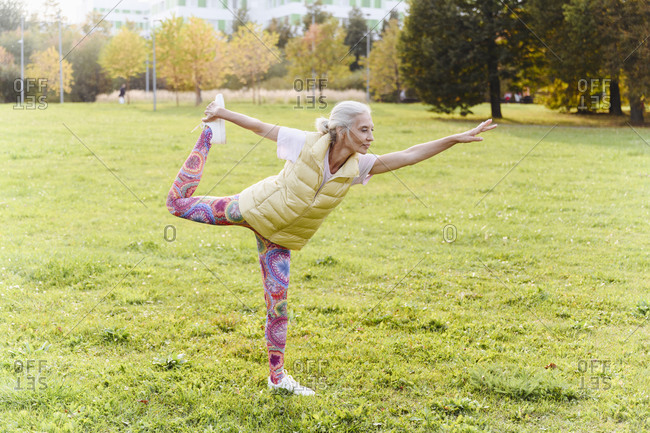 Mature woman doing yoga exercise on grass in public park