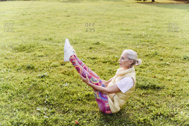 Mature woman practicing yoga on grass in public park