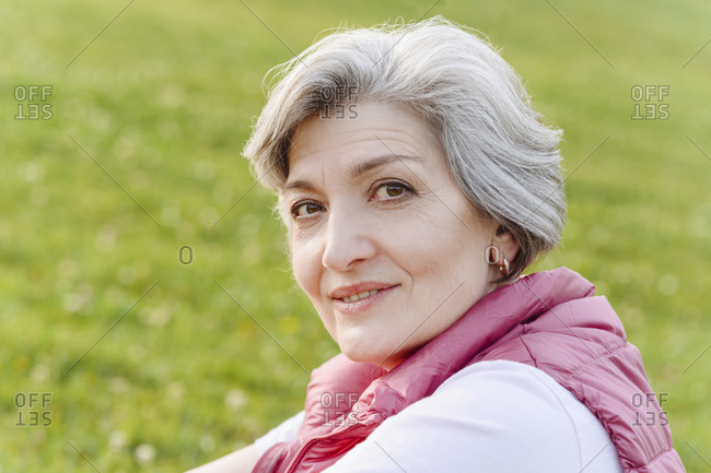 Smiling mature woman with gray hair at public park