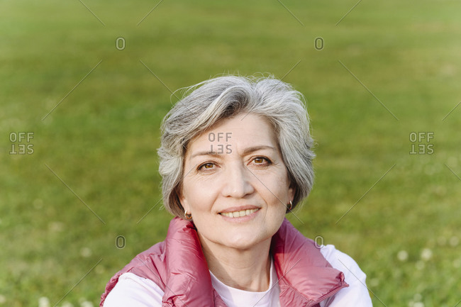 Smiling mature woman at public park on sunny day