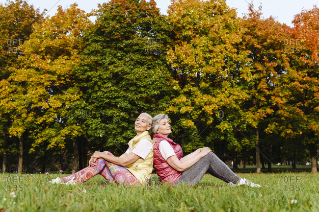 Mature female friends with eyes closed leaning on each others back at autumn park