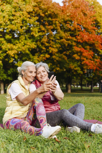 Smiling mature female friends in sports clothing taking selfie at autumn park