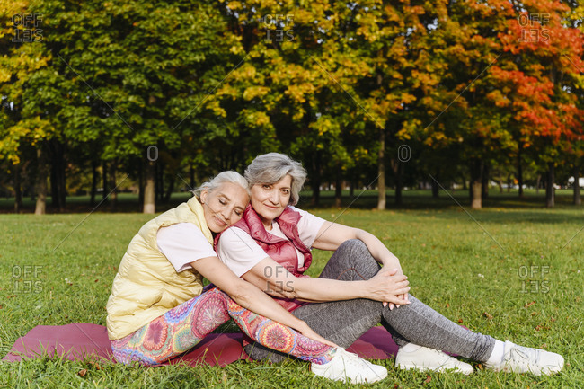 Mature woman resting with eyes closed on female friends shoulder at public park