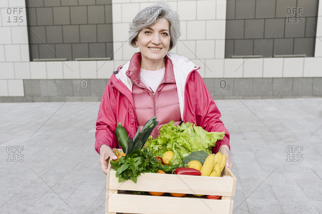 Smiling mature woman with vegetable and food crate against wall