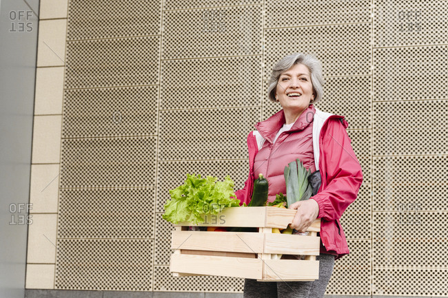 Happy mature woman with food crate against iron pattern wall