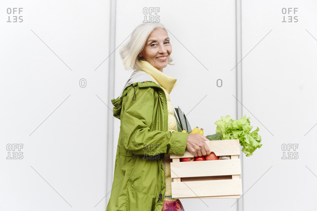 Smiling mature woman walking with healthy food crate against wall