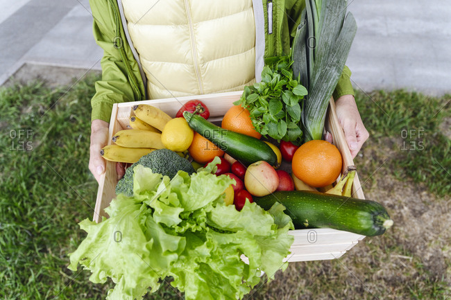 Mature woman with wood crate filled with healthy food over grass