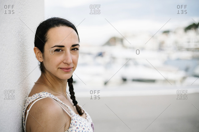 Mid adult woman leaning on white wall during sunset in city
