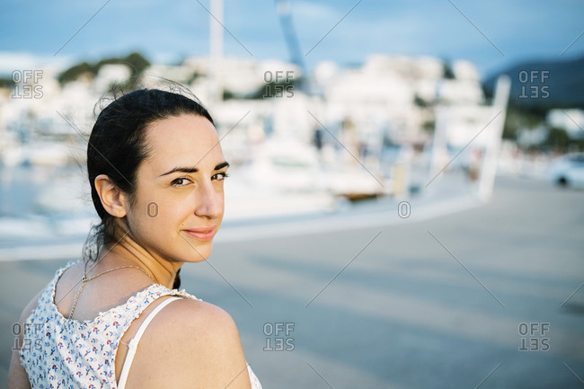 Smiling woman in city during sunset