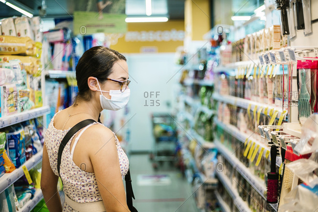 Mid adult woman with protective face mask in supermarket