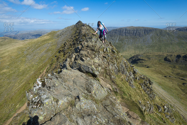A woman careful makes her way along Striding Edge towards Helvellyn int he Lake District of England