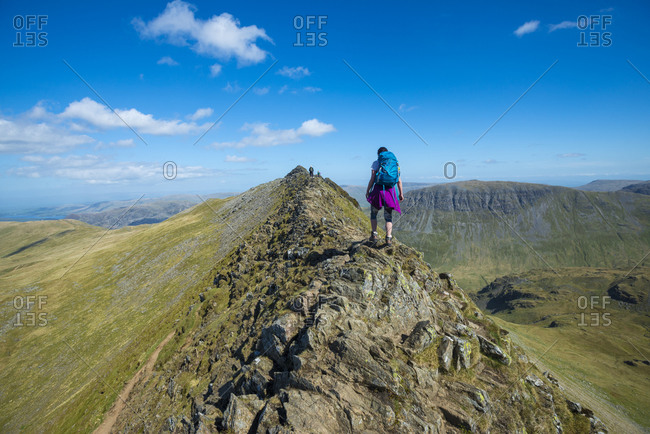 A woman stands on top of Striding Edge facing towards Ullswater in the English Lake District