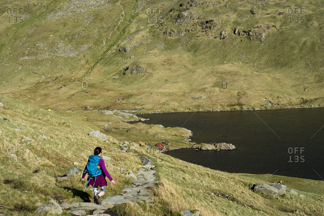 A woman trekking in the Lake District in England makes her way down the  trail from Helvellyn to Grisedale Tarn