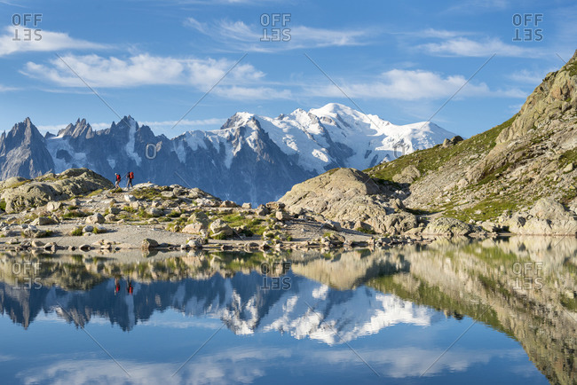 Hikers and the summit of Mont Blanc reflected in Lac Blanc on the Tour du Mont Blanc trekking route in the French Alps