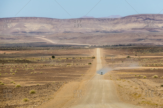 A 4x4 car leaves a cloud of dust as it approaches along the long dusty road to the Fish River Canyon in Namibia