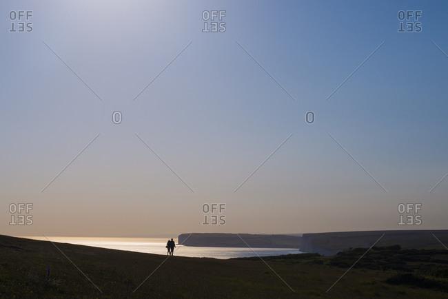 A couple walking along the South Downs near Beachy Head in Britain