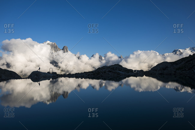 A hiker reflected in Lac Blanc on the Tour du Mont Blanc trekking route in the French Alps