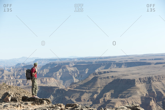 A man stands on the edge of the Fish River Canyon in Namibia