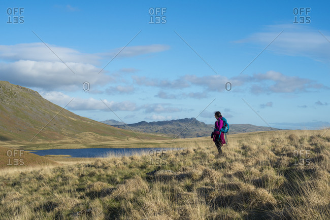 A woman trekking in the English Lake District in Wast Water looks towards Burnmoor Tarn