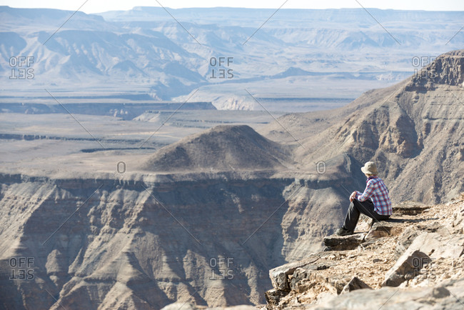 A woman sits on the edge of the Fish River Canyon in Namibia