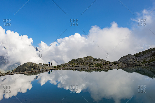 Hikers reflected in Lac Blanc on the Tour du Mont Blanc trekking route in the French Alps