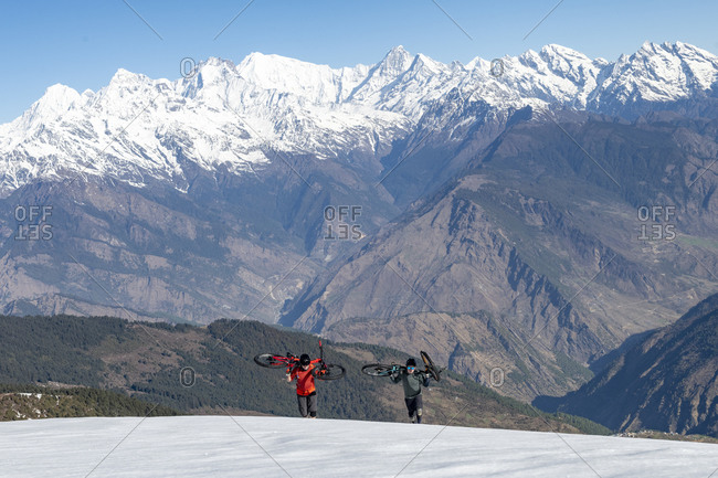 Mountain bikers carry their bikes up a snow covered slope in the Himalayas with views of the Langtang range in the distance