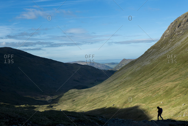 A hiker in the Lake District in England makes her way down the  trail from Grisedale Tarn to Patterdale