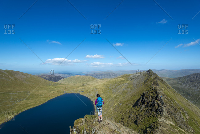 A woman stands on top of Striding Edge facing towards Red Tarn in the English Lake District