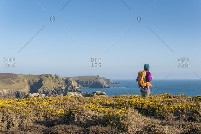A woman looks out over dramatic Cornish coastline near Land's End at the westernmost part of the British Isles