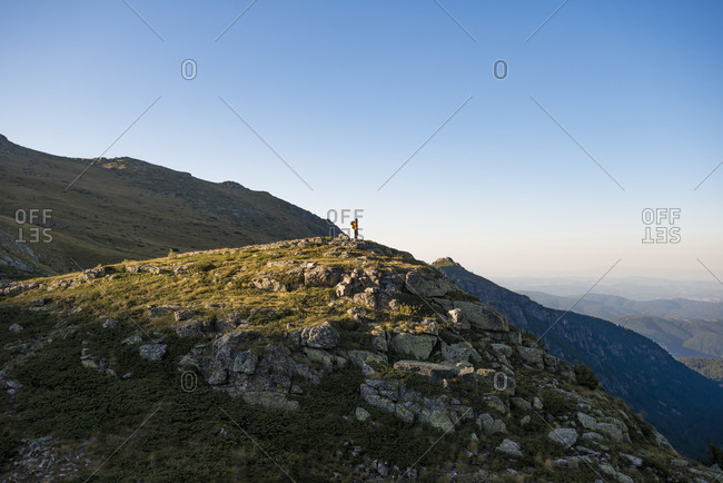 A hiker stands on top of a hill at sunset in the Rila mountains with views down to the valleys below
