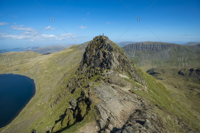 Trekkers on top of Striding Edge with a view of Red Tarn below in the Lake District of England