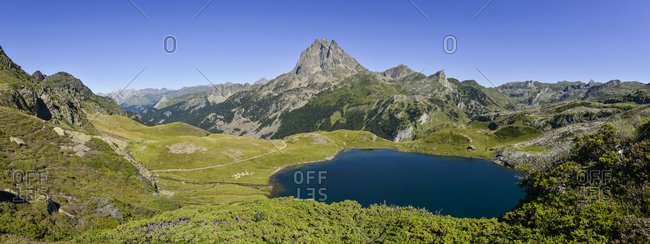 A panoramic view of Lac du Miey and Pic Midi d'Ossau and the GR10 hiking trail leading off into the distance