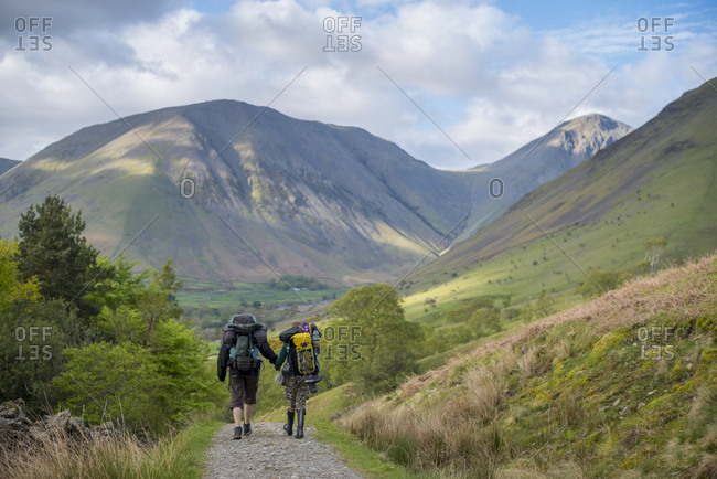 Wast Water, The Lake District, Cumbria, UK - May 25, 2015: Walkers in the English Lake District return from Burnmoor Tarn to Wast Water with a view of Kirk Fell and Great Gable in the distance
