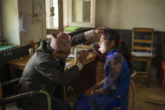 A doctor looks inside a woman's mouth with a torch in Diktel hospital in Nepal