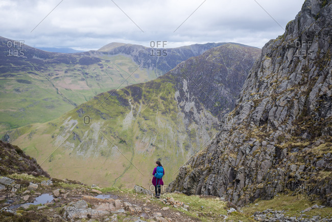 A hiker in the Lake District in England standing near the top of Haystacks above Butteremere with a view of Fleetwith Pike in the distance