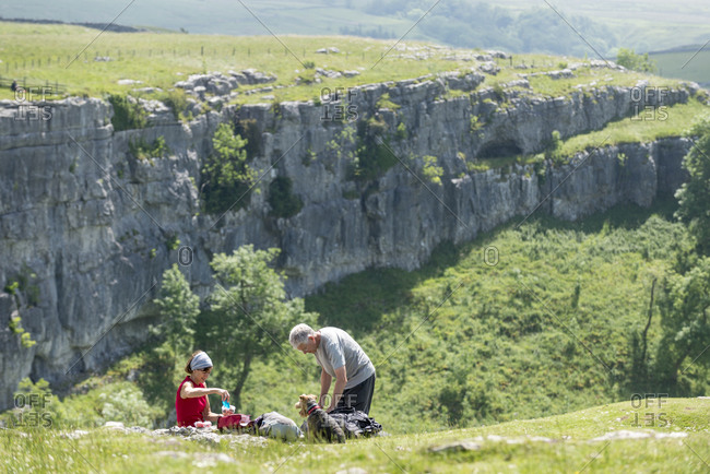 A couple hiking the Pennine Way stop for a picnic at Malham Cove in the Yorkshire Dales National Park with their Welsh Terrier dog