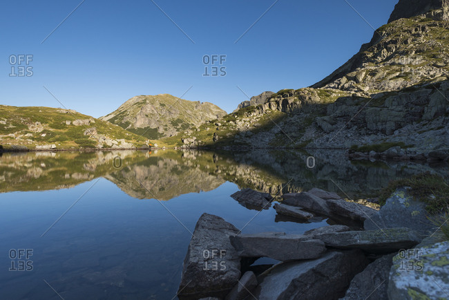 Hiking next to a flat calm lake making a mirror reflection in the Rila mountains