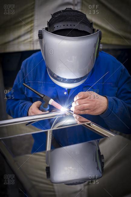 Suffolk Yacht Harbour, Levington, Ipswich, Suffolk, UK - March 5, 2015: Metal fabricator welding a steel canopy on a boat