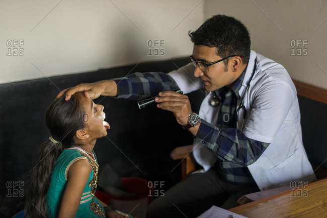 A doctor looks inside a little girls mouth with a torch in Diktel hospital in Nepal