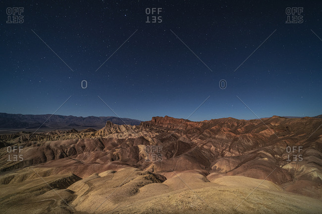 A man looking out at surreal rock formations caused by erosion at Zabriskie Point moonlit under a bright night sky full of stars