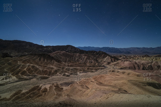 Surreal rock formations caused by erosion at Zabriskie Point moonlit under a bright night sky full of stars
