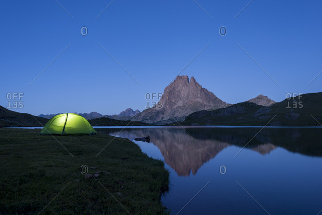 A tent glows green at twilight beside Lac Gentau with Pic Midi d'Ossau reflected in the lake next to the GR10 trekking route in the Pyrenees