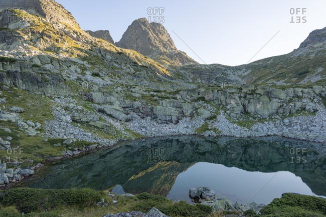 A lake in the Rila mountains beneath Maliovitsa peak makes a mirror reflection