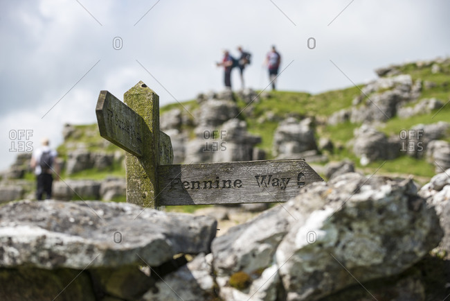A sign for the Pennine Way with distant hikers blurred in the background near Malham Cove in the Yorkshire Dales National Park