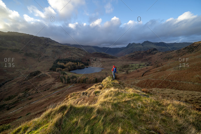 A woman hiking from Lingmoor Fell looks out to Blea Tarn and the Langdale Pikes in the English Lake District