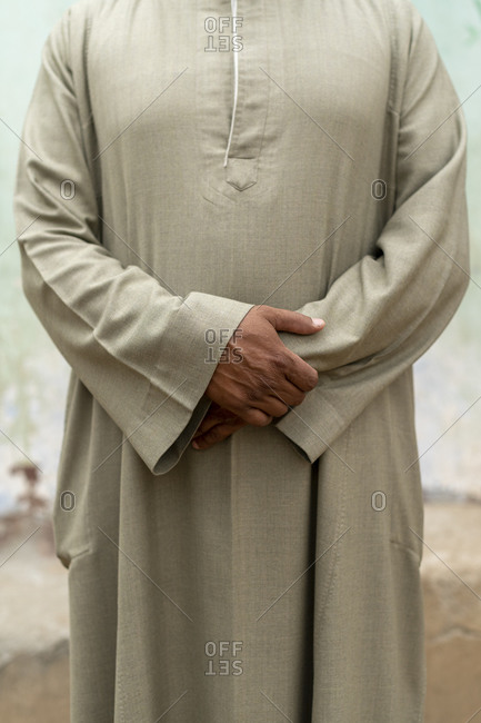 An Egyptian man wearing traditional clothes holding his hands his with arms folded