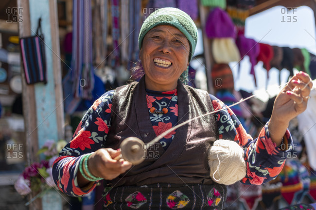 A Sherpa woman from Gosainkund spins baby Yak wool using the traditional method with a spindle