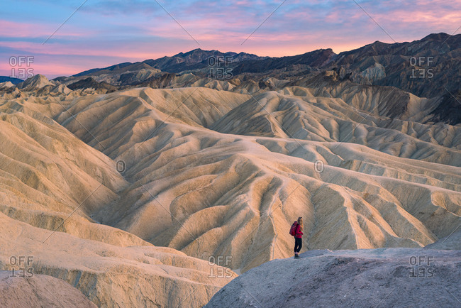 A girl hiking on a trail near Zabriskie Point in Death Valley near Natural rock formations caused by erosion